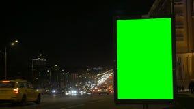 Um quadro de avisos com uma tela verde em uma rua movimentada Luzes coloridas lightsBlurred coloridas borradas vídeos de arquivo