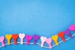Um quadro dos corações de madeira coloridos que penduram em uma corda em um CCB azul Imagens de Stock Royalty Free