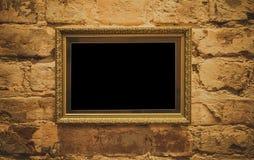 Um quadro dourado com um baguette decorativo bonito pendura em uma parede antiga dourada fotografia de stock