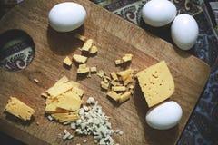 Um queijo e um alho do corte com ovos estão na placa de corte na tabela Foto de Stock