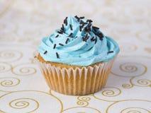 Um queque azul em um tablecloth foto de stock