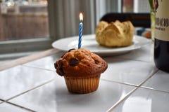 Um queque do aniversário com vela imagens de stock