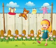 Um quintal com roupa de suspensão e uma rapariga Imagem de Stock Royalty Free