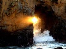 Um raio da luz do sol é considerado da caverna do mar em Big Sur, CA Imagem de Stock