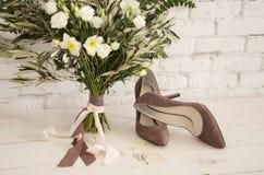 Um ramalhete bonito das flores e das sapatas Imagens de Stock Royalty Free