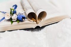 Um ramalhete da noiva das rosas e das alianças de casamento brancas e azuis do ouro imagem de stock