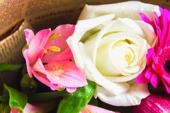 Um ramalhete das flores de um lírio, de um gerbera, de umas rosas brancas e de um alstroemeria em uma tabela de madeira branca Um Fotos de Stock Royalty Free