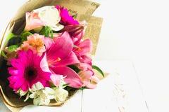 Um ramalhete das flores de um lírio, de um gerbera, de umas rosas brancas e de um alstroemeria em uma tabela de madeira branca Um Foto de Stock