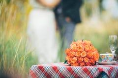 Um ramalhete das flores em uma tabela do casamento do grupo com uma noiva e um gro Fotografia de Stock