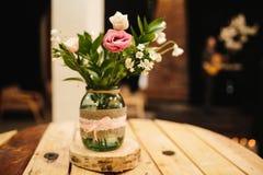 Um ramalhete das flores está no banco, a rosa está no foco, tudo mais é um pouco obscuro fotografia de stock royalty free