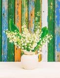 Um ramalhete das flores perfumadas brancas da floresta dos lírios do vale em um jarro branco Fotos de Stock Royalty Free