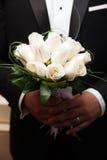 Um ramalhete das rosas brancas nas mãos da noiva Imagem de Stock Royalty Free