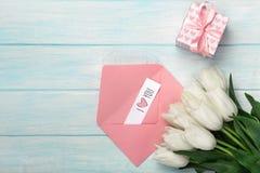 Um ramalhete das tulipas brancas com uma caixa de presente, uma nota do amor e um envelope da cor em placas de madeira azuis foto de stock royalty free
