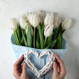 Um ramalhete das tulipas brancas no papel de envolvimento azul com mãos e coração da mulher em um fundo concreto branco Vista sup Imagens de Stock Royalty Free