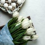 Um ramalhete das tulipas brancas no papel de envolvimento azul com a placa com ovos em um fundo concreto branco Vista superior Co Foto de Stock