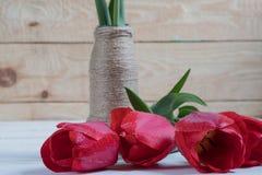Um ramalhete das tulipas em uma tabela de madeira imagens de stock royalty free