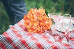 Um ramalhete de flores alaranjadas e cor-de-rosa com os cálices do vinho que encontram-se sobre Foto de Stock Royalty Free