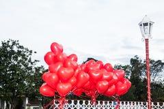 Um ramalhete de flutuação de balões vermelhos, coração-dados forma Fotografia de Stock Royalty Free