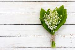 Um ramalhete de lírios perfumados das flores do vale no fundo de madeira branco com espaço da cópia Imagem de Stock Royalty Free