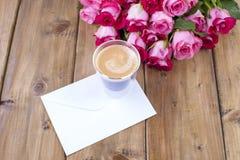 Um ramalhete de rosas cor-de-rosa frescas e de um vidro do café Fundo de madeira Espaço livre para o texto ou os cartão Envelope  Foto de Stock