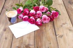 Um ramalhete de rosas cor-de-rosa frescas e de um vidro do café Fundo de madeira Espaço livre para o texto ou os cartão Envelope  Imagem de Stock Royalty Free