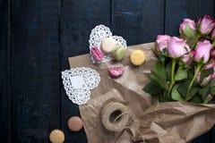 Um ramalhete de rosas cor-de-rosa no papel marrom Dois corações e biscoitos brancos do macarrão Espaço livre para o texto ou os c Fotos de Stock Royalty Free