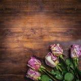 Um ramalhete de rosas listradas no canto de uma tabela de madeira escura velha Vista da parte superior Lugar para o texto Fotos de Stock Royalty Free