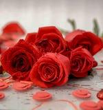 Um ramalhete de rosas vermelhas encontra-se em uma tabela branca entre os corações fotos de stock royalty free