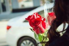 Um ramalhete de três rosas vermelhas nas mãos da menina Close-up imagens de stock royalty free