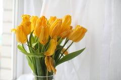 Um ramalhete de tulipas amarelas em um vaso na soleira Um presente t Fotos de Stock Royalty Free