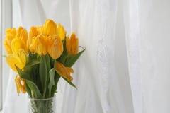 Um ramalhete de tulipas amarelas em um vaso na soleira Um presente t Imagem de Stock Royalty Free