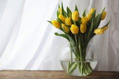 Um ramalhete de tulipas amarelas em um vaso na soleira Um presente t Fotos de Stock