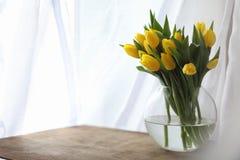 Um ramalhete de tulipas amarelas em um vaso na soleira Um presente t Foto de Stock