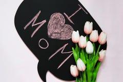Um ramalhete de tulipas cor-de-rosa encontra-se em um quadro preto com o ins Foto de Stock Royalty Free