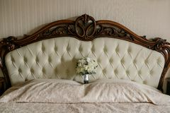 Um ramalhete do casamento das rosas brancas e das orquídeas brancas está na cabeça da cama Foto de Stock