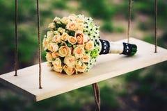 Um ramalhete do casamento das rosas encontra-se em um balanço de madeira na natureza Fotos de Stock