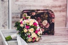 Um ramalhete do casamento encontra-se em uma tabela de madeira ao lado de uma mala de viagem bonita Imagem de Stock Royalty Free