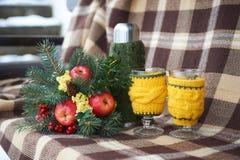 Um ramalhete do inverno ao lado de uma garrafa e dos copos de garrafa térmica para o chá Fotografia de Stock Royalty Free