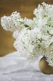 Um ramalhete do lilás branco em um potenciômetro de argila em um fundo de madeira close-up, foco macio imagens de stock royalty free
