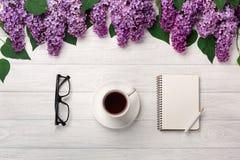 Um ramalhete dos lilás com o copo do chá, do caderno e dos vidros nas placas brancas fotografia de stock royalty free
