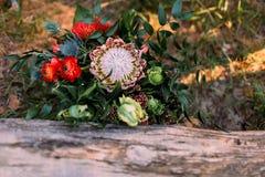 Um ramalhete rústico do casamento com as fitas cor-de-rosa perto do log artwork Imagem de Stock Royalty Free