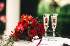 Um ramalhete vermelho, uns vidros bonitos com champanhe e um descanso para as alianças de casamento encontram-se na tabela Foto de Stock