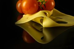 Um ramo de tomates de cereja com uma fatia de queijo de Edamer fotos de stock royalty free