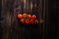 Um ramo de tomates de cereja orgânicos vermelhos em um fundo de madeira Imagem de Stock