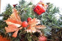 Um ramo de uma árvore verde do ano novo decorada com os presentes vermelhos, pequenos, os brinquedos, as folhas douradas e a bola Imagem de Stock