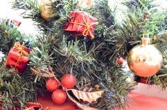 Um ramo de uma árvore verde do ano novo decorada com os presentes vermelhos, pequenos, os brinquedos, as folhas douradas e as bol Imagens de Stock