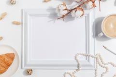 Um ramo do algodão e uma xícara de café com leite em um fundo claro Vista superior Copie o espaço foto de stock royalty free