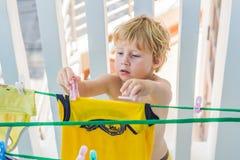 Um rapaz pequeno ajuda sua mãe a pendurar acima veste-se Foto de Stock