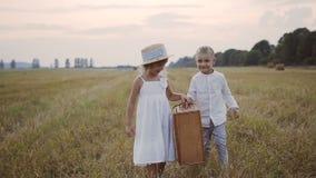 Um rapaz pequeno ajuda uma menina a vestir uma mala de viagem da palha em um vestido branco Caminhada das crianças no campo Por d video estoque
