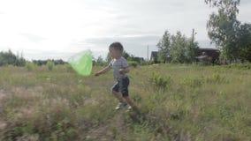 Um rapaz pequeno alegre corre com uma rede para uma borboleta video estoque